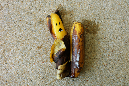 Banana with Scared - Rotten Bananas Face on Concrete Background Great For Any Use. Stock Photo