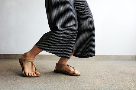 피트 여자 착용 샌들과 블랙 바지. 모든 사용에 대 한 좋은 시멘트 배경에 서있는 여성.