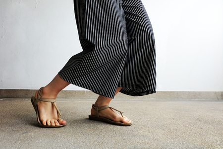 Feet Woman Wear Sandals and Black Pants. Female Standing on The Cement Background Great For Any Use.