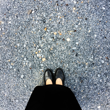skirts: Close Up on Womans Feet Wearing Black Sandals & Dress, Standing Commemorate on Stone Great For Any Use. Stock Photo