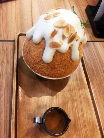 Korean Dessert - Bingsu Milk Tea Ice Shave and Pouring Tea on Wooden Table Background Great For Any Use.