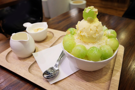 Melon Korean Shaved Ice Cream Vanilla Dessert on Tray with Topping and Milk on Wooden Table Background Great for Any Use.