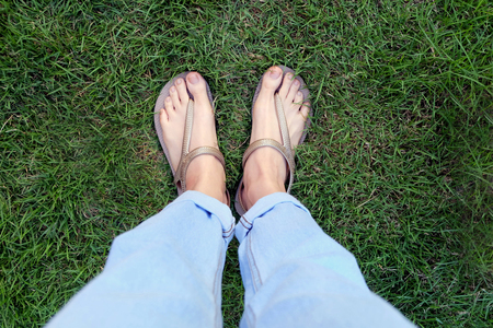 Close Up Woman's Legs and Feet Wearing Flip Flops on the Green Grass Background Great for Any Use.