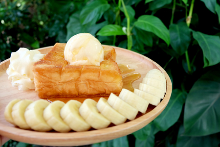 Honey Toast with Banana and Vanilla Ice Cream on Wooden Salver. Close Up Bread Buttered Toast with Whipped Cream Dessert on Wood Dish Background Great for Any Use.