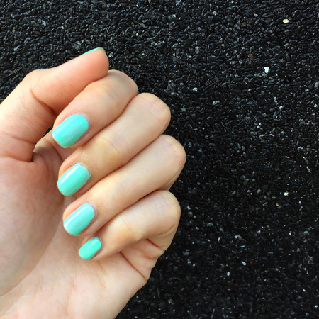 Green Manicure Nail. Beautiful Female's Hand Nails Polish on the Concrete Wall Background Great for Any Use.