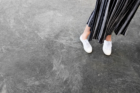 White Sneakers Shoes. Woman is Legs in White Sneaker and Pants on the Concrete Street Background Great for Any Use.