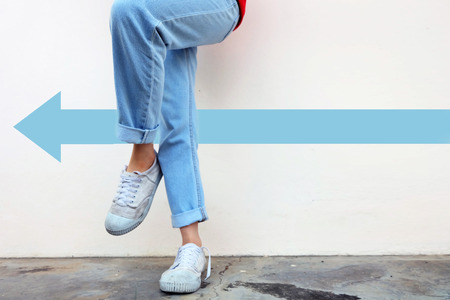 White Shoes Concept. Female Wearing White Sneakers with Blue Arrows Line Direction on Concrete Road Background Great for Any Use.