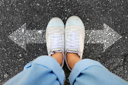 Woman Wear White Sneakers and Blue Jeans with Two Arrows Different Direction on Concrete Road Background