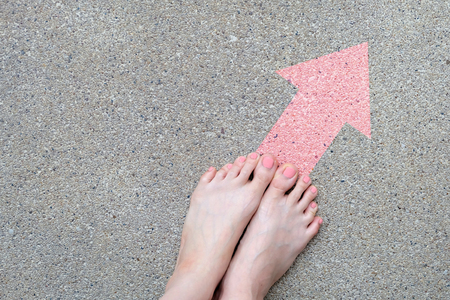 Feet on the Pink Arrow Drawn Top View. Female Bare Foot with Pink Nail Polish Manicure On Floor Street Road Background Great for Any Use. 스톡 콘텐츠