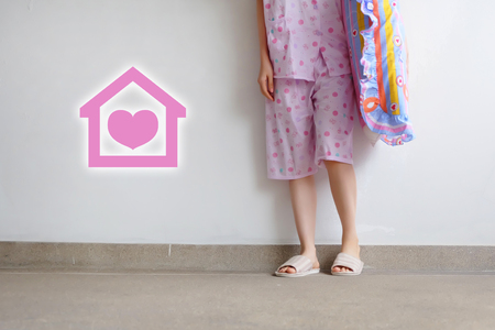 Checkered Warm Slipper with Pink Heart Home Icon. Feet and Legs Female Standing in Pink Pajamas Pants and Shoes Holding A Pink Pillow on Floor Background Great For Any Use.