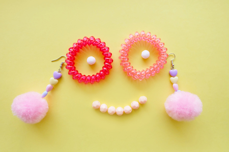 Face Smile Spiral Rubber Bands Fashion Accessories. Pink Heart Earring Isolated of Different Color Bead on Yellow Background Great For Any Use. Stock Photo