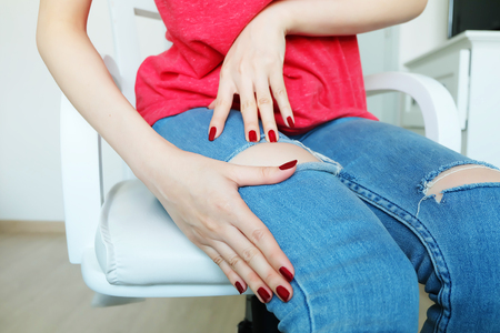 Close Up Red Nails Manicure Cosmetics. Beautiful Woman with Red Nail Polish and Red Shirt Sitting on a White Chair Background Great for Any Use. Stock Photo
