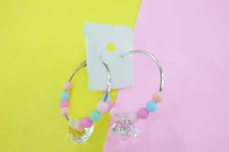 Hoop Earring Fashion Accessories. Colorful Bead Earrings Isolated on Pink and Yellow Pastel Background Great for Any Use. Stock Photo