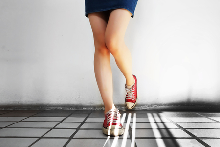 Red Sneakers of Free Space. Beautiful Slim Woman Legs with Red Shoes and Jean Skirt on Floor Background Great for Any Use.