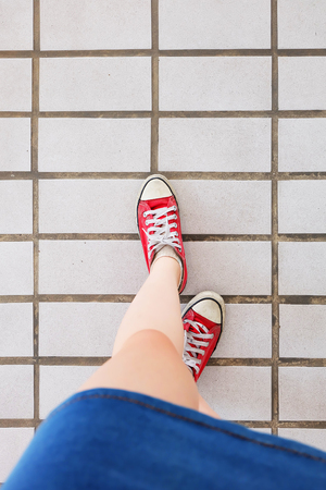 Selfie of Sneakers. Woman Wearing Jean Skirt and Red Shoes on Tile Background Great for Any Use.