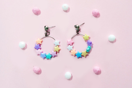Colorful Hoop Earring Fashion Accessories. Hoop Earrings with Star Bead Isolated on Pink Pastel with Bead Background Great for Any Use.