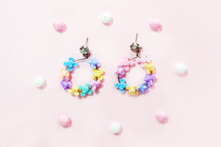 Jewelry Hoop Earring Fashion Accessories. Hoop Earrings with Flower Bead Isolated on Pink Pastel with Bead Background Great for Any Use. Stock Photo