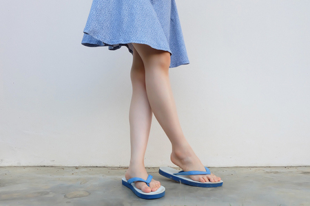 Selfie Girl Slim Legs Blue Shoes and Dress Isolated on Concrete Floor. Woman Standing Wearing Blue Flip Flop (Sandal) on The Cement Floor Background Great For Any Use.