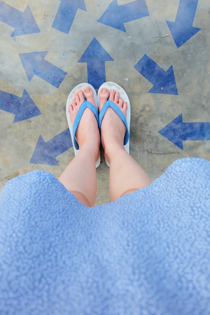 Arrow Different Decisions. Selfie Blue Flip Flop Isolated on Concrete Floor from Above. Female Standing Wearing Blue Shoes and Blue Dress with Arrows Choices Direction on The Cement Background Great For Any Use.