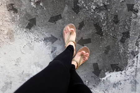 Many Direction Arrow Choices. Gold Shoes Isolated on Concrete Floor,Top View. Woman Standing is Feet Wearing Flip Flop (Sandal) on The Cement Floor Background Great For Any Use. Stock Photo