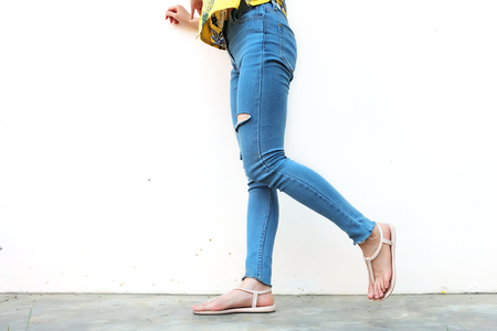 Summer Fashion Nude Sandal (Footwear) and Slim Legs in The City,Street Style. Beautiful Slim Woman Legs with Nude Sandals and Lack Blue Jean on Concrete Floor Background Standard-Bild