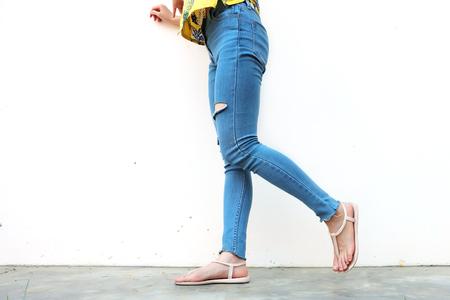 Summer Fashion Nude Sandal (Footwear) en Slim Legs in The City, Street Style. Mooie slanke vrouwenbenen met naakte sandalen en gebrek aan blauwe jeans op betonnen vloer achtergrond