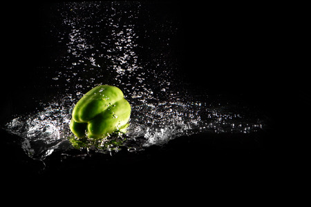 Fresh Green Bell Pepper with Water Splash and Bubble Isolated. Pepper Copy Space. Juicy Green Paprika Dropped Falling into Water on Black Background