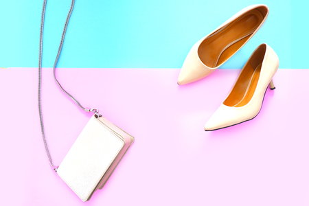 Beautiful Nude Ladies Leather Bag and Stylish High-Heels Shoes Isolated in Pastel Colored. Fashionable Womens Accessories Flat lay, Top View. Female Sandals (Shoe) in Pink and Blue Color Background.