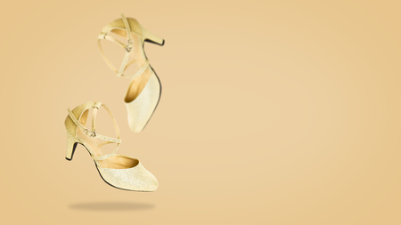 719ee03134e3b Beautiful Falling Pair of Golden High Heels Shoes Isolated on Bright Beige  Color Background. Beauty