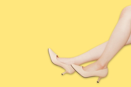 Beautiful Asian Woman Legs Wearing Summer Beige High Heels Shoes Isolated On Yellow Background with Clipping Path. Side View of Sexy Female Leg in Luxury High-Heeled Sandals. A Model and Fashion Shoe. Stock Photo