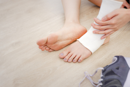 Woman Foot with Gauze Elastic Bandage and Purple Shoes (Sneakers). Hands on Sports Injury. Unrecognizable Injured Legs & Feet on Pain Area Sitting on a Wooden Floor Background from Rupture or Tear.