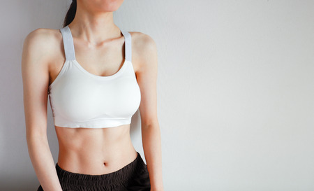 Fitness and Yoga Healthy Lifestyle Concept. Young Woman Wearing White Sport Bra and Pants with Muscular Body and Strong Six Pack Abs. Female Posing in Sportswear (Sports Clothes) on Gray Background.