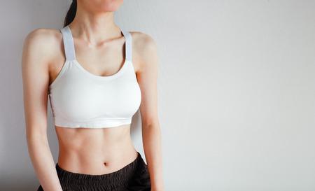 Fitness- und Yoga-gesundes Lifestyle-Konzept. Junge Frau mit weißem Sport-BH und Hose mit muskulösem Körper und starken Sixpack-Bauchmuskeln. Weibliche posiert in Sportbekleidung (Sportbekleidung) auf grauem Hintergrund.