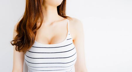 White Tank Top on a Young Woman. Female is Breast in Underwear Posing on Grey Background. Show the Bra. Sexy Girl Wearing Striped Shirt with Perfect Chest. Fitness and Beauty Fashion Concept. 免版税图像