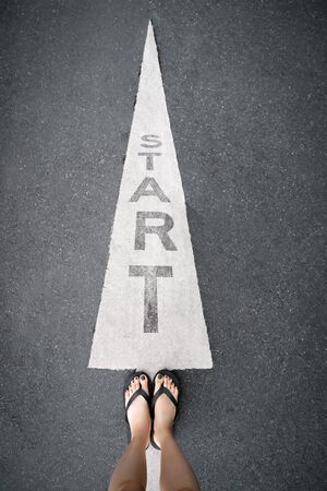 Feet and Arrow on Road of Starting Point. Word Start Written on an Asphalt Concrete with Legs and Shoes. Woman Bare Feet with Gray Nail Polish Manicure Standing on the Road Background to Future Life.