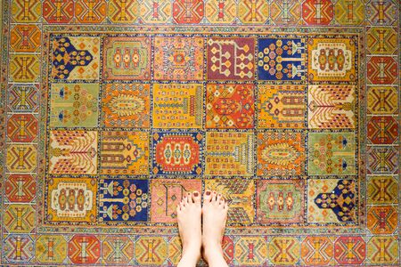 Iran Carpet Texture. Young Woman Feet Standing on Vintage Colorful Carpet with Barefoot.