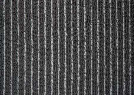 Carpet texture in office, full frame concept. Close up of monochrome grey carpet background or pattern from above. Top view. Industrial gray color fitted rug. Black mat textile of Interior element.