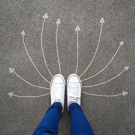 Voeten en pijlen op de weg. Oplossing. Selfie vrouw witte schoenen of sneakers dragen op concrete achtergrond met pijlen. Succes, creatief, keuze en idee concept. Bovenaanzicht. Voet en benen van bovenaf gezien.