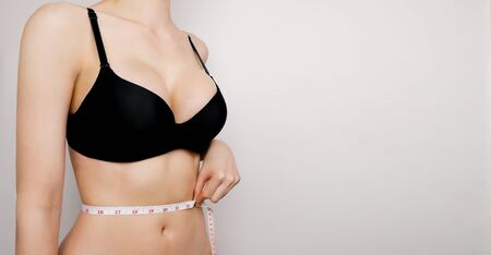 Diet and weight loss design concept. Sexy woman with big breast in black lingerie bra. Fit fitness female measuring her waist with a measure tape on gray background. Slim body care, healthy lifestyle.