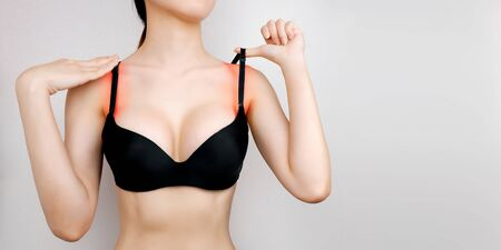 Checking strap on lingerie. Woman in black bra on gray background. Female with irritated or painful skin under brassiere. Healthcare and problem concept. Hands on injured shoulder on pain area