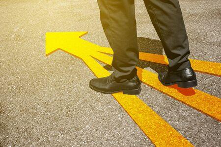 Uomo d'affari in tuta in piedi sul pavimento con il simbolo della freccia gialla. Vista dall'alto. Selfie di piedi in scarpe di pelle nera su sfondo strada dall'alto. Uomini d'affari che vanno avanti, inizio e concetto di successo.