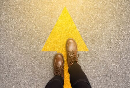 Feet and arrows on road background in starting line beginning idea. Top view. Woman in leather ankle boots on pathway with yellow direction arrow symbol. Moving forward, new start and success concept.
