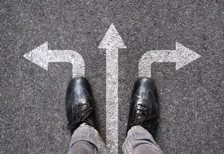 Feet and arrows on road background. Selfie feet above. Businessman standing on pathway with three direction arrows choice or move forward. Top view of business shoes walking. Motivation and growth. Stock Photo