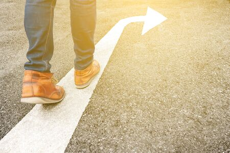 Feet and arrow on asphalt road background in starting line beginning idea. Selfie above view of hipster in boots or brown shoe standing on pathway. Top view. Moving forward, new start and success.