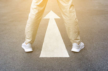 Guide of feet arrow on road background. Man in casual shoes standing on asphalt. Concept of new start, choice business, way to success and beginning of life. Forward sign on street. 스톡 콘텐츠