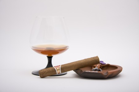 tipple: It is a picture of my imagine luxury lifes illustration. There is an expensive cognac, and costly cuban cigar, intresting ashtray... Well, it is an expensive treat