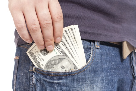 putting money in pocket: human hand is putting money in the pocket Stock Photo