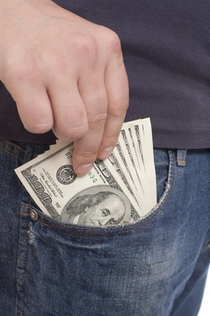 human hand is putting money in the pocket Stock Photo