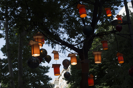 Adorned street trees. There are decorative balls, balloons, lamps and oil lamp Stok Fotoğraf
