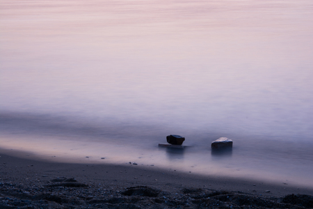 the sea has become silky. two rocks on the sea surface